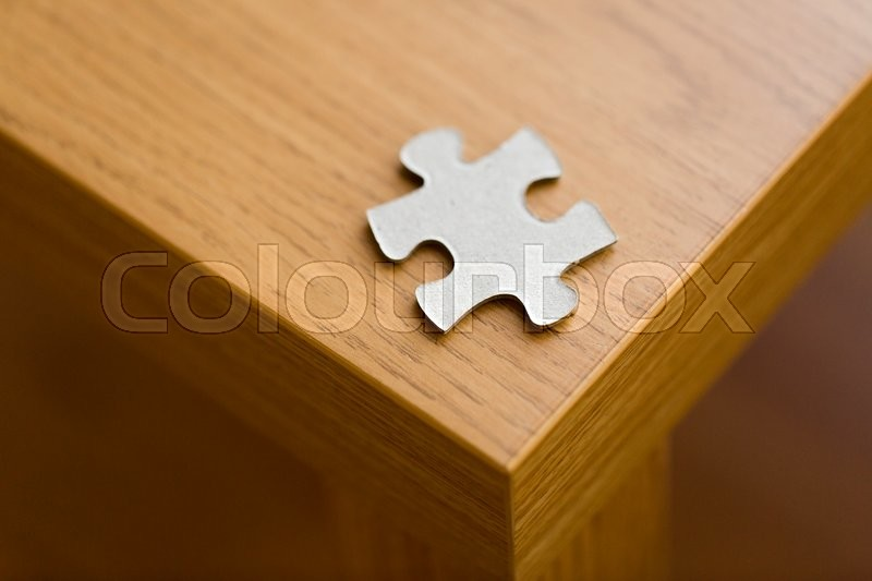 Stock image of 'business and connection concept - close up of puzzle piece on wooden surface'