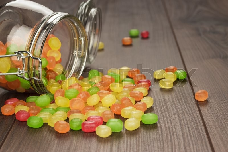 Stock image of 'toppled over glass jar full of colorful sweets on the wooden table'