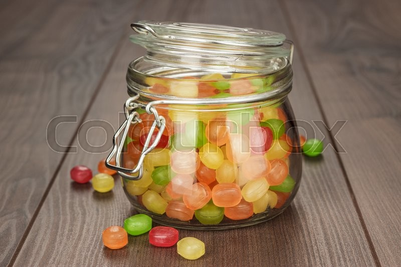 Stock image of 'glass jar full of colorful sweets on the wooden table'