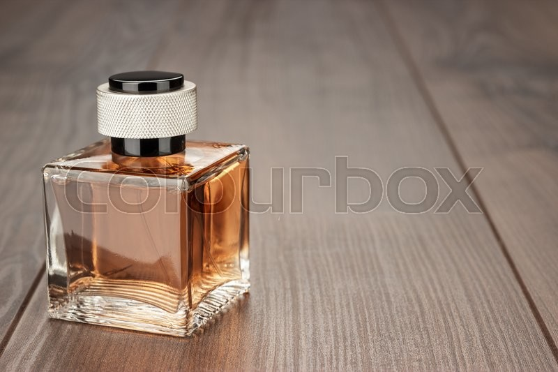 Stock image of 'perfume bottle on the brown wooden table background'