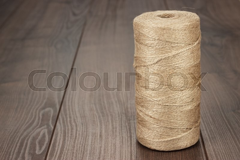 Stock image of 'reel of durable thread on the wooden table'