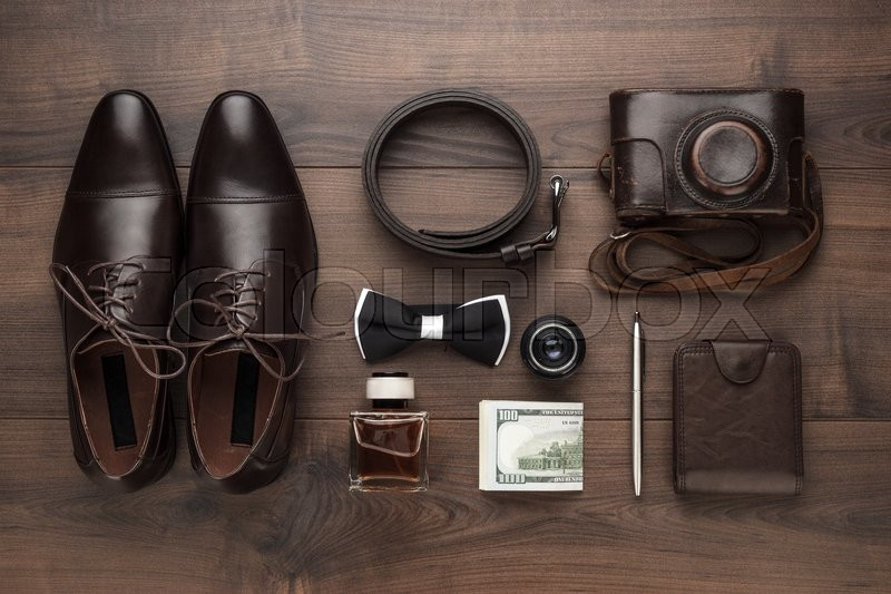 Stock image of 'men's accessories in order on the brown wooden table overhead view'