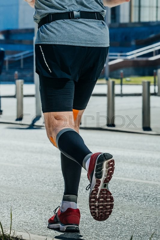 Stock image of 'closeup of legs of a runner. running through streets of city'