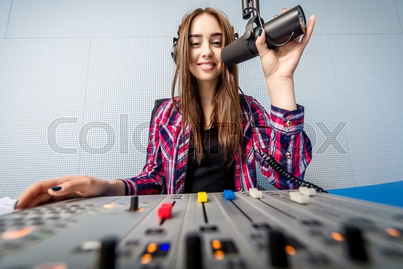 Stock image of 'female dj working in front of a microphone on the radio'
