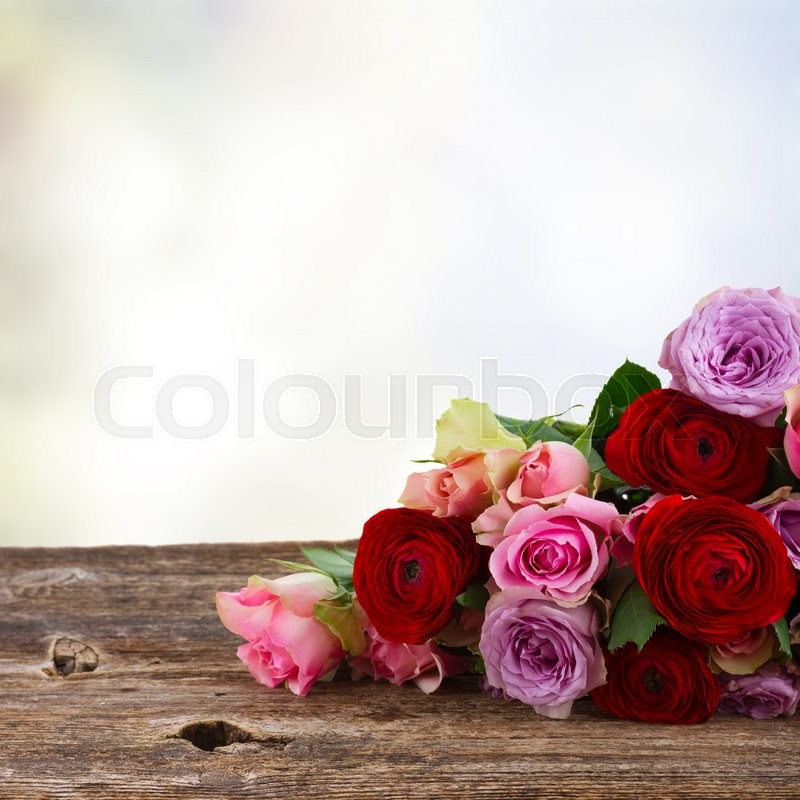Stock image of 'bouquet of fresh roses and ranunculus on wood blue bokeh in background'