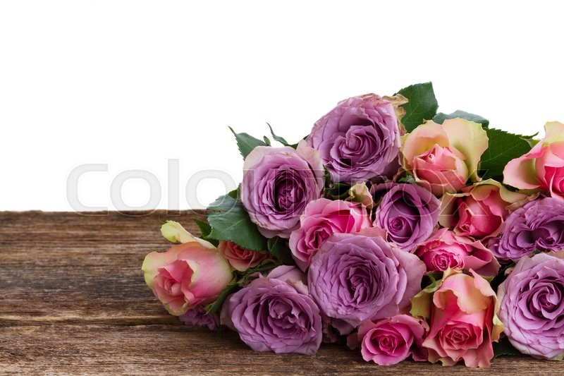 Stock image of ' pink and violet  fresh roses on wooden background border over white '