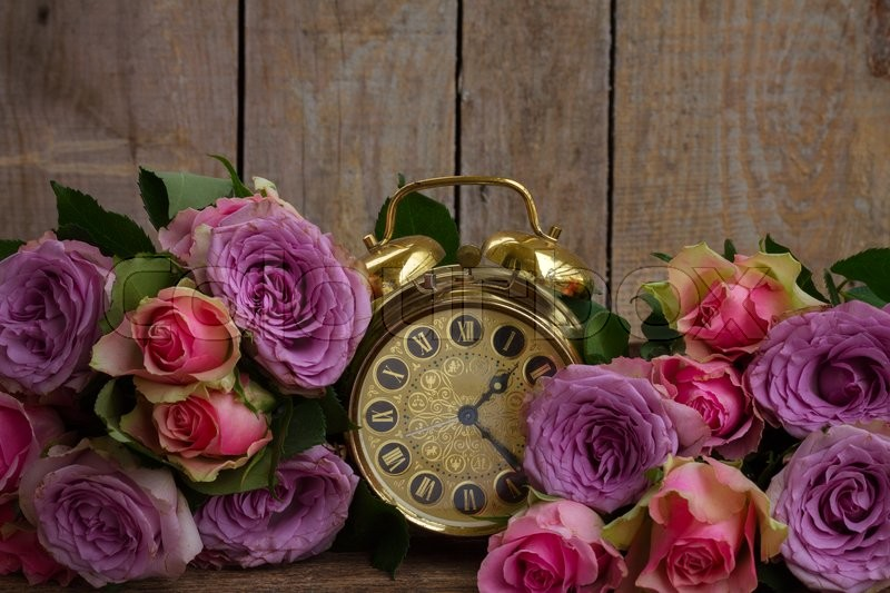 Stock image of 'bouquet of pink and violet  fresh roses with golden vintage clock on wood '