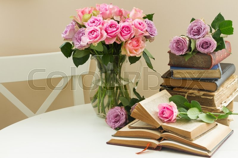 Stock image of 'Pile of old books with bouqet of  rose flowers'