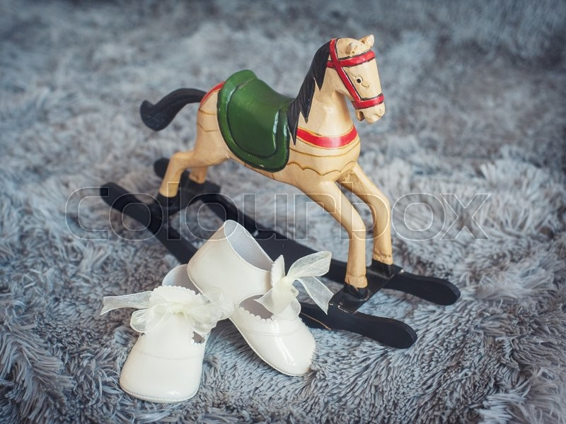 Stock image of 'Children's shoes and children's toy rocking horse'