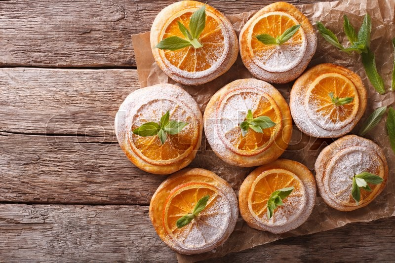 Stock image of 'Homemade cookies with almonds and oranges close-up paper on the table. Horizontal view from above\'