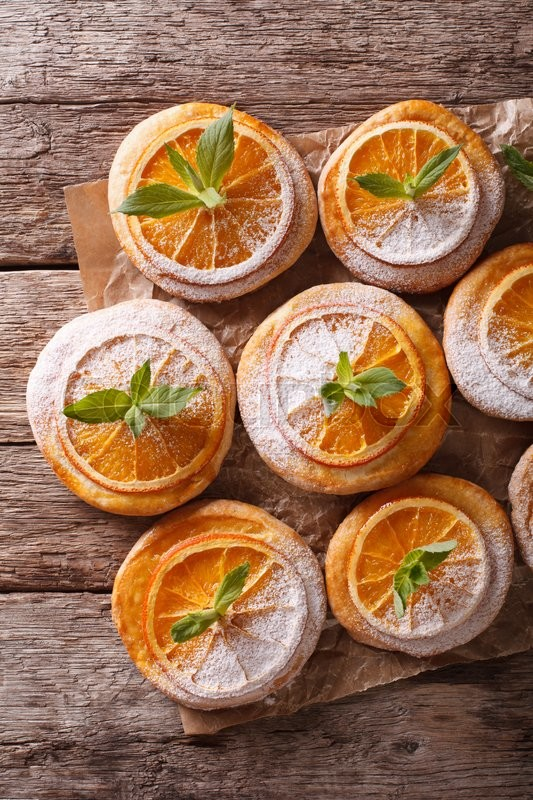Stock image of 'Orange cookies with mint and powdered sugar close-up on the paper on the table. vertical view from above\'