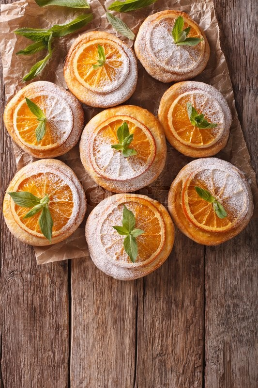 Stock image of 'Homemade cookies with almonds and oranges close-up paper on the table. vertical view from above\'