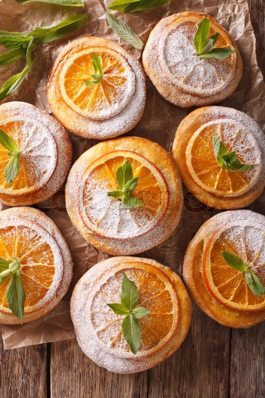 Stock image of 'cookies with orange slices and mint close-up paper on the table. vertical view from above\'