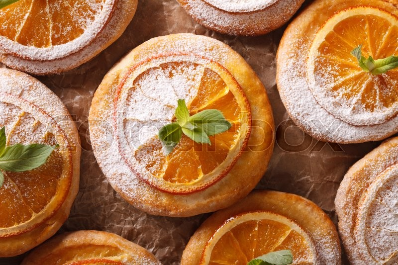 Stock image of 'Almond biscuits with orange slices and mint on a table macro. horizontal view from above\'