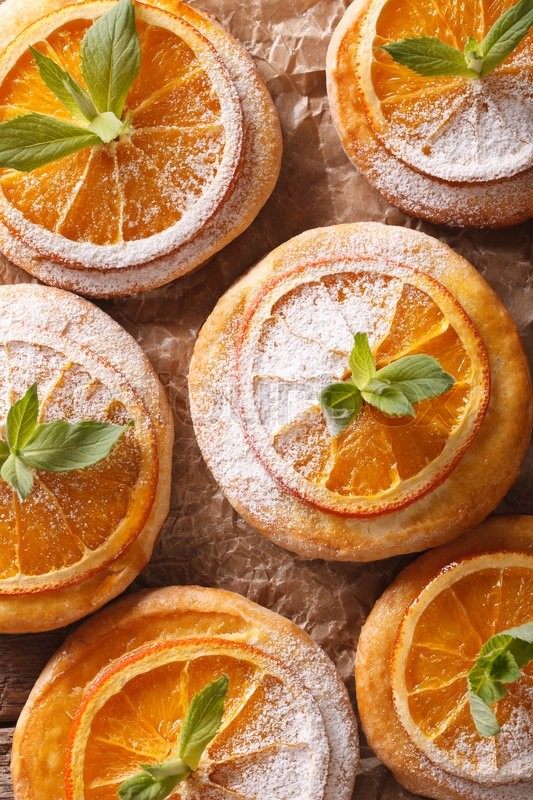 Stock image of 'Almond biscuits with orange slices and mint on a table macro. Vertical view from above\'