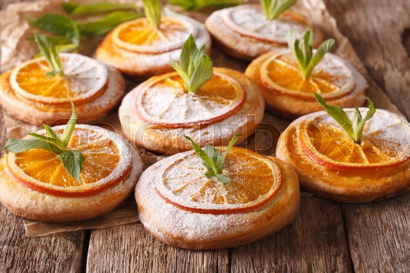 Stock image of 'Almond biscuits with orange slices and mint close-up on the table. horizontal\'