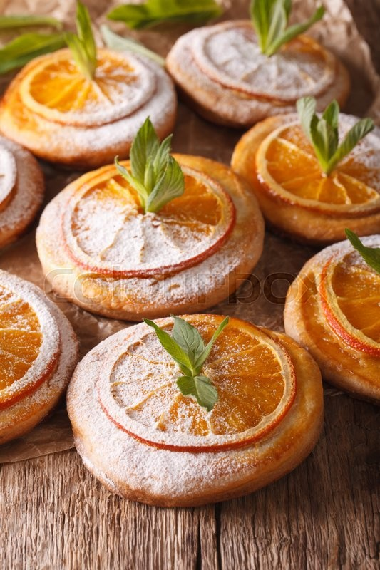 Stock image of 'Freshly baked cookies with oranges and mint close-up on the table. Vertical\'