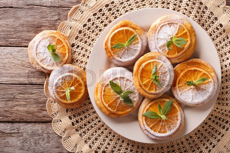 Stock image of 'Tasty cookies with oranges, decorated with mint and powdered sugar close-up on a plate. Horizontal view from above\'