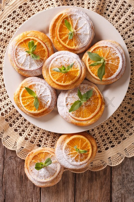 Stock image of 'Tasty cookies with oranges, decorated with mint and powdered sugar close-up on a plate. Vertical view from above\'