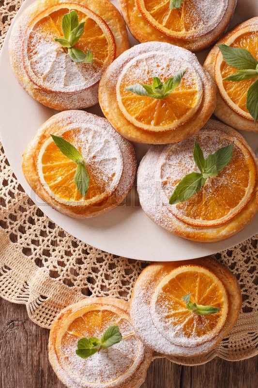 Stock image of 'Homemade cookies with almonds and oranges closeup on a plate. Vertical view from above\'