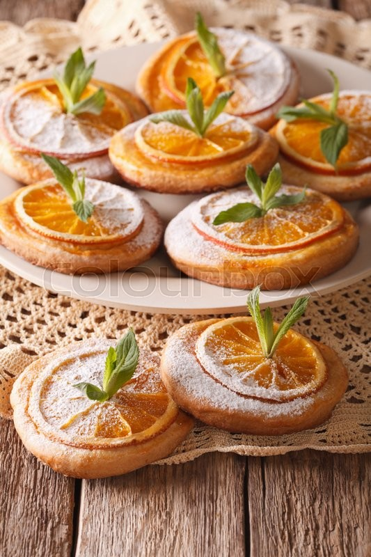 Stock image of 'Tasty cookies with oranges, decorated with mint and powdered sugar close-up on a plate. Vertical\'
