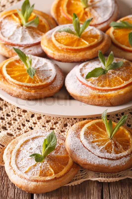 Stock image of 'Festive fresh baked biscuits with orange close-up on a plate. Vertical\'