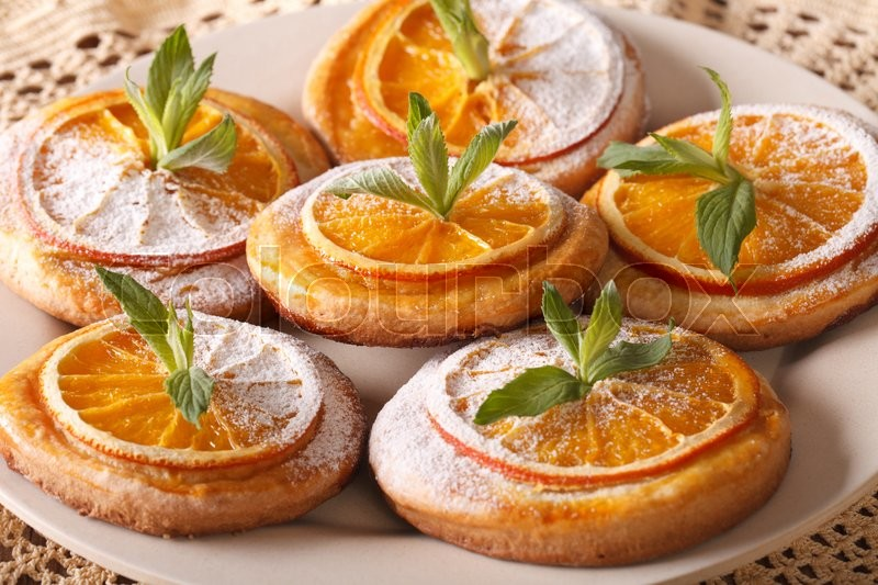 Stock image of 'Tasty cookies with oranges, decorated with mint and powdered sugar close-up on a plate. horizontal\'
