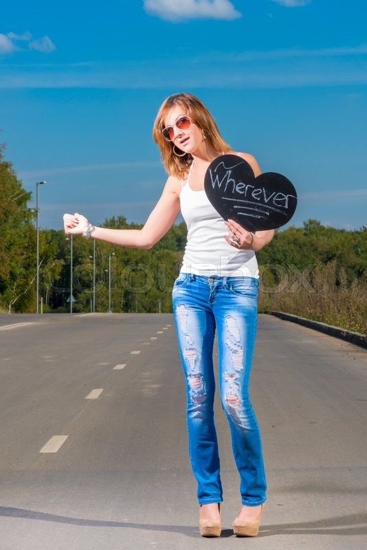 Stock image of 'Young girl hitchhiking on a country road'