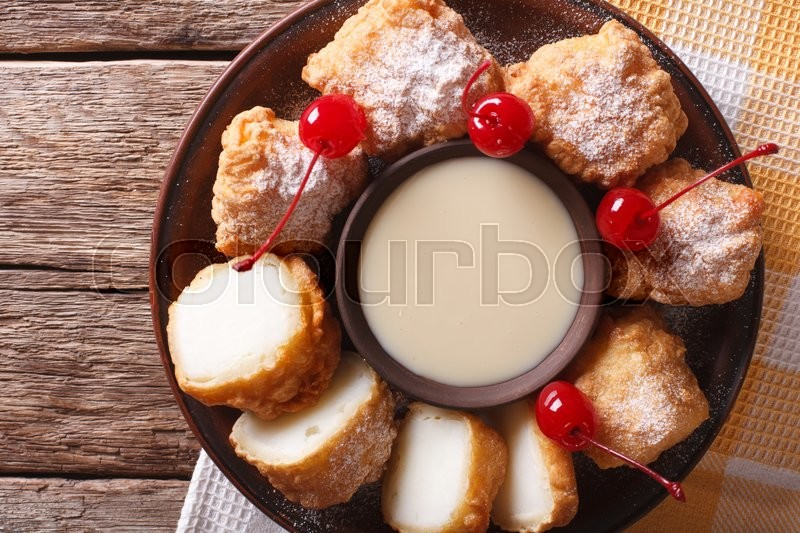 Stock image of 'Dessert Leche frita with condensed milk and cherries on a plate closeup. Horizontal view from above\'