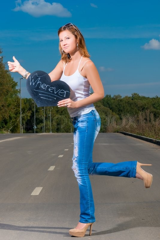 Stock image of 'Woman in jeans and t-shirt of 30 years old travels hitchhiking'