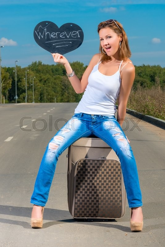 Stock image of 'Beautiful young girl with a suitcase on the road'