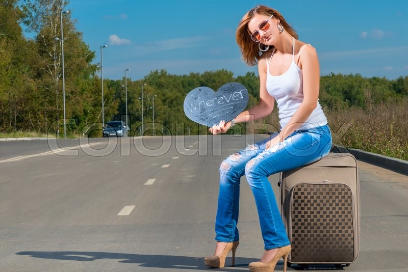 Stock image of 'Hitchhiking girl sitting on a suitcase and waiting for a car'