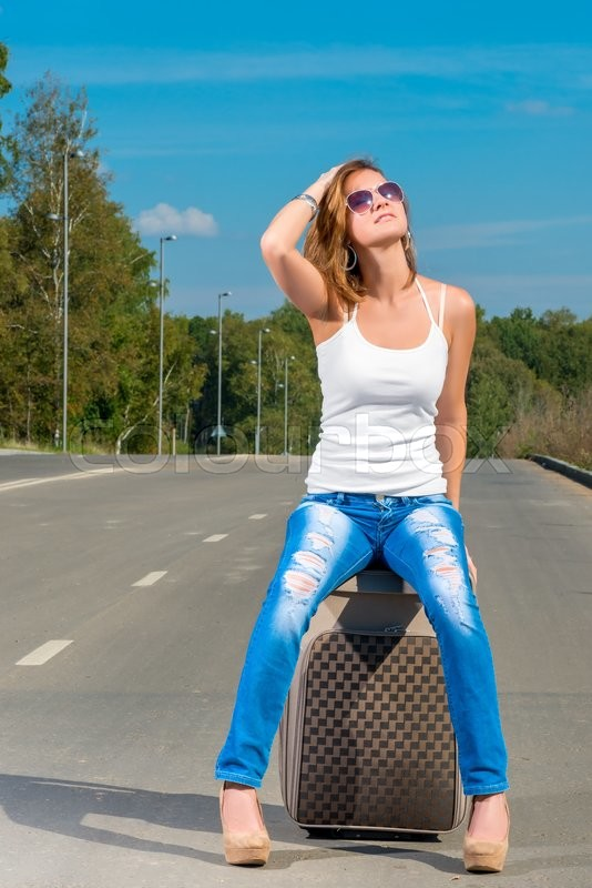 Stock image of 'Young girl traveling across the country with a suitcase hitchhiked'