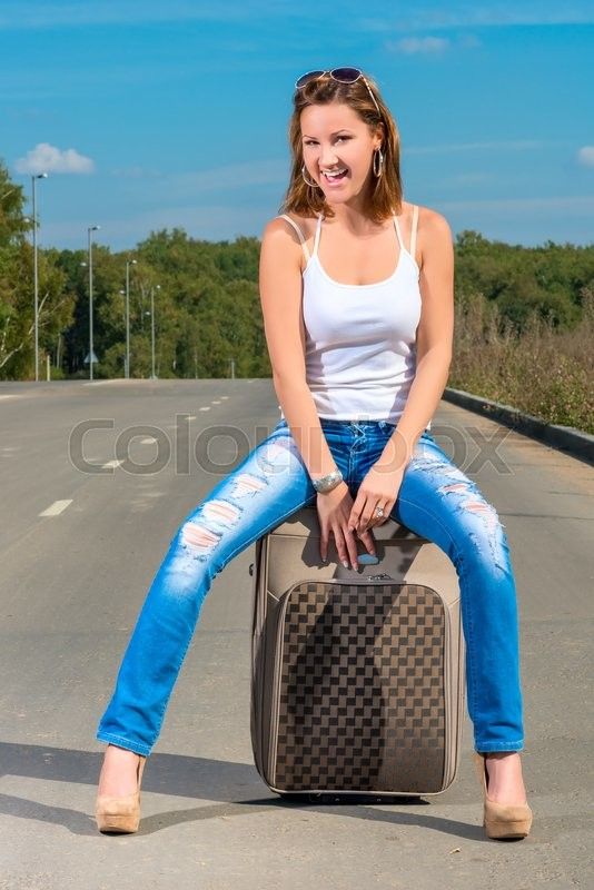 Stock image of 'Happy girl with a suitcase on the road on a sunny day'