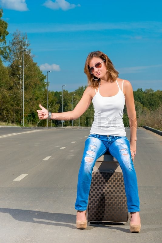 Stock image of 'Girl shooting with a suitcase on the road car'
