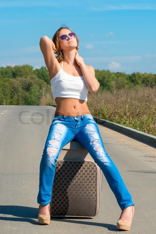 Stock image of 'Woman sunbathing on a suitcase on the road'