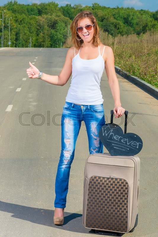 Stock image of 'Girl with a suitcase on the road traveling hitchhike'