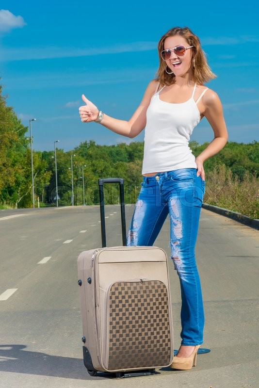 Stock image of 'Positive woman hiker with big suitcase on the road'
