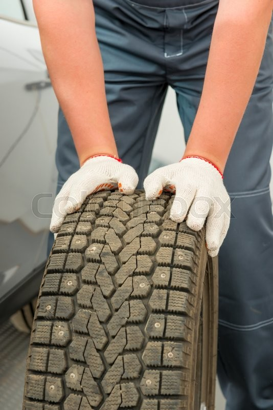 Stock image of 'Car tire and mechanic hand gloves closeup'