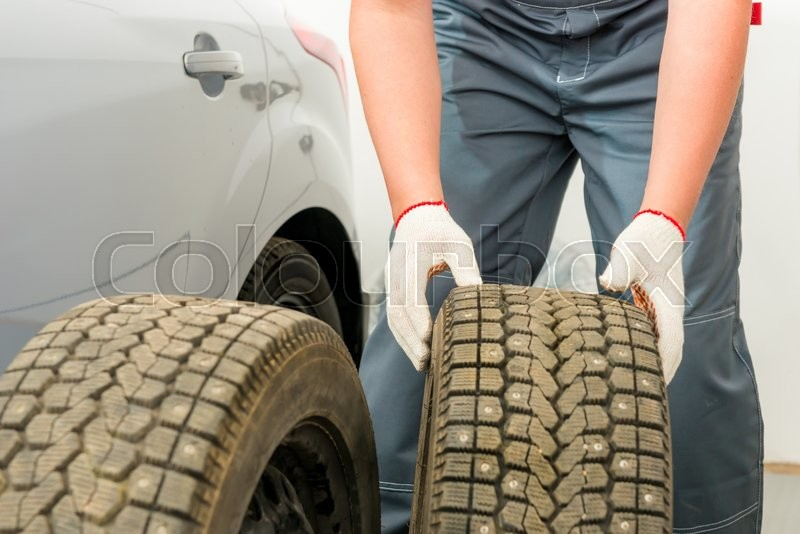 Stock image of 'Mechanic is preparing a Tire fitting service wheels'
