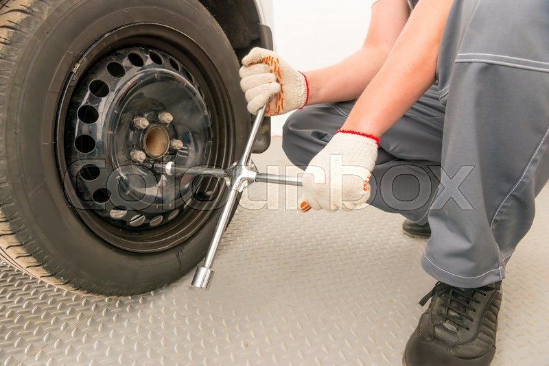 Stock image of 'Mechanic unscrews the wheel a wrench, close-up shot'