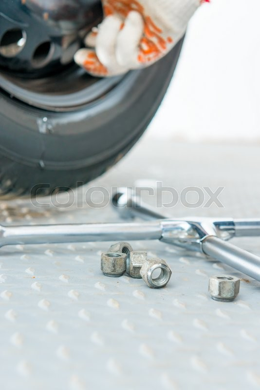 Stock image of 'Wrench and nuts close-up in a garage'