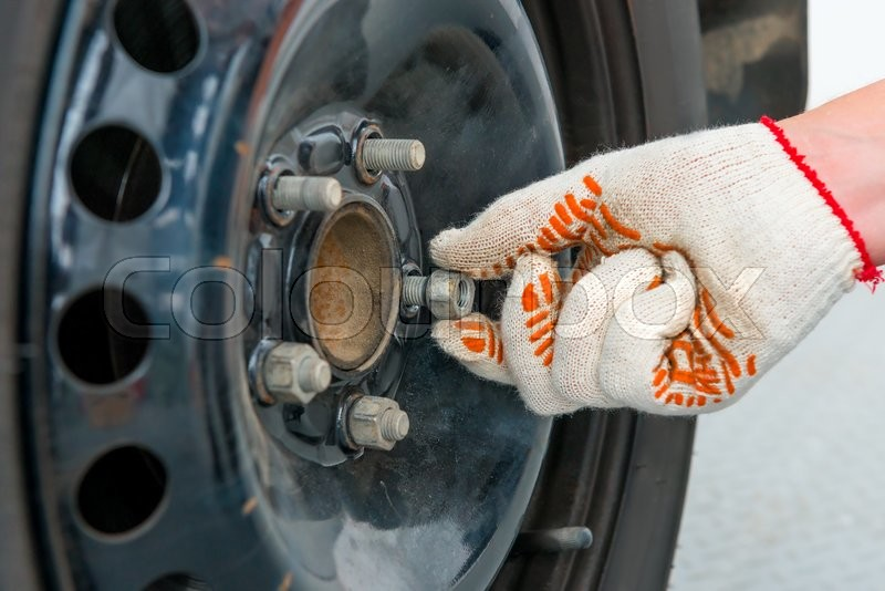 Stock image of 'Man's hand unscrews the nuts on the car wheel, close-up shot'