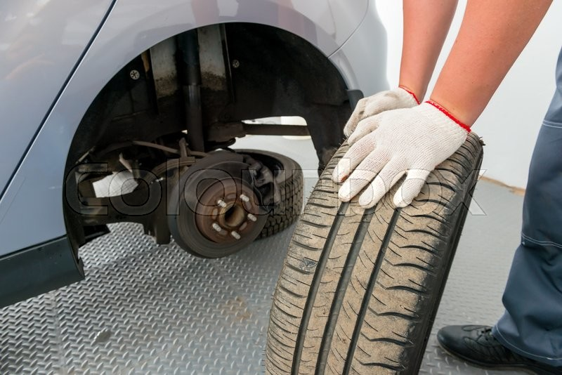 Stock image of 'A man with a huge wheel mechanic near the car'