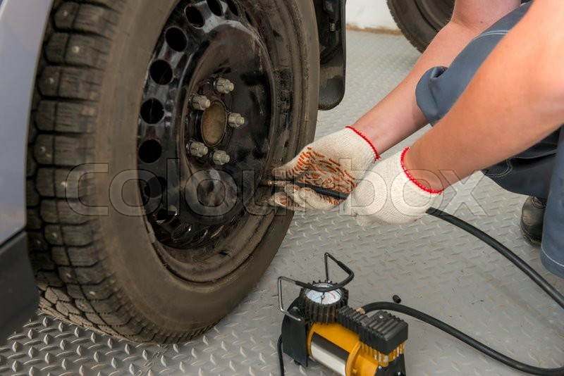 Stock image of 'Mechanic pump inflates the the wheel in garage'
