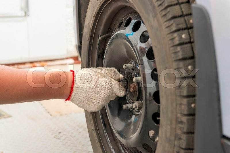 Stock image of 'Man's hand tightening the screws on the wheel after installation'