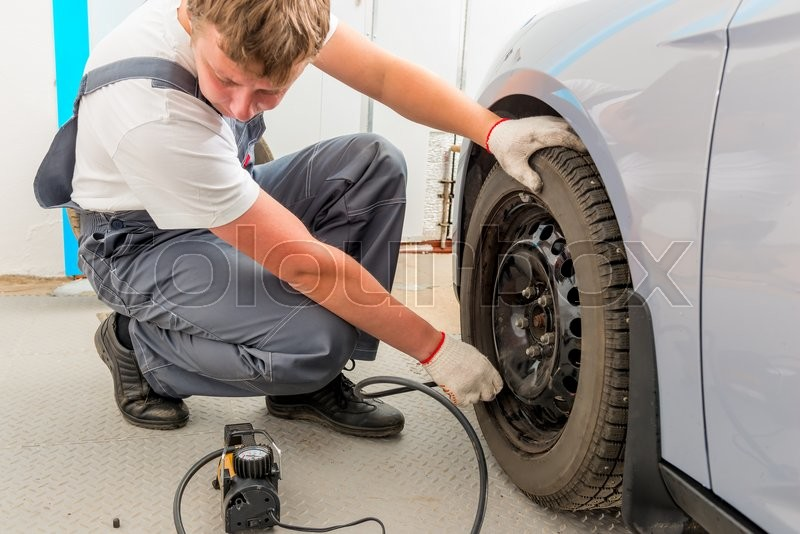 Stock image of 'Mechanic checks the degree of the wheel pump'