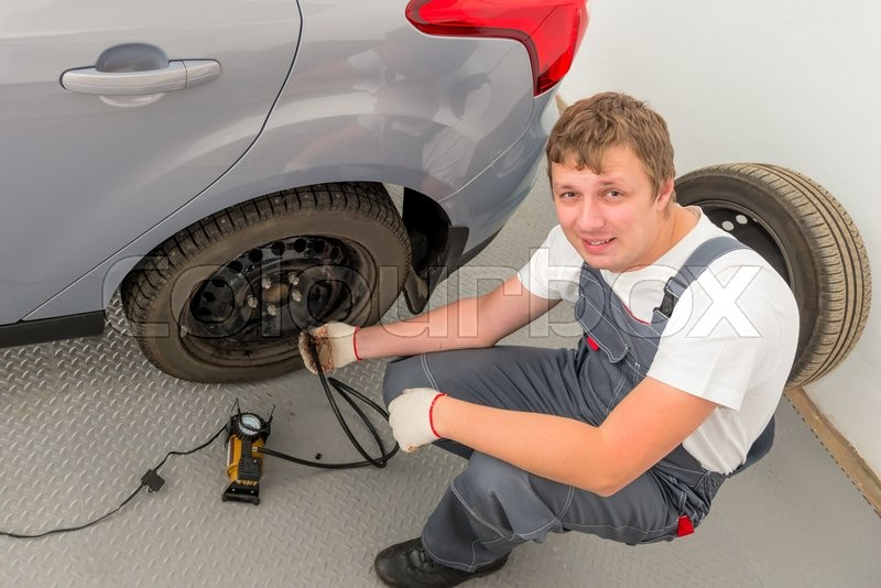 Stock image of 'Smiling mechanic a pump inflates the the wheel in garage'