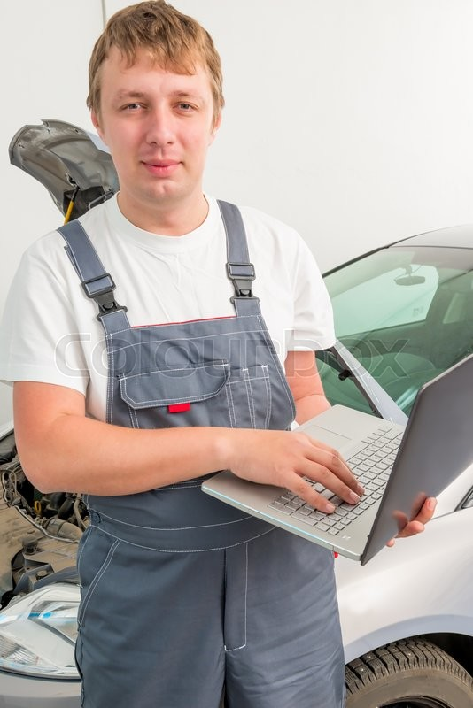 Stock image of 'Engineer of mechanics with a laptop near a car in a garage'