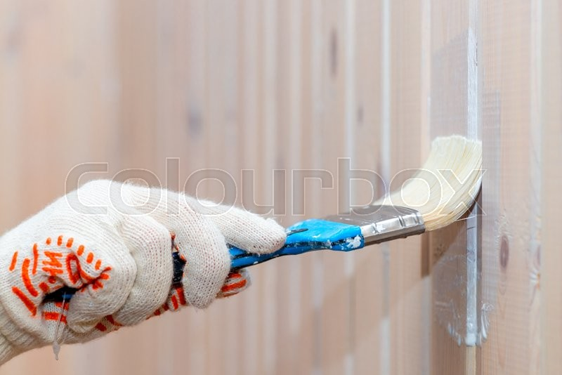 Stock image of 'Hand in glove paint the wooden wall protective paint'
